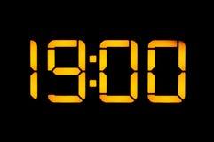 O pulso de disparo digital eletrônico com números alaranjados em um fundo preto mostra que o tempo dezenove zero zera na noite Is foto de stock