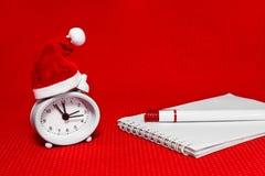 O pulso de disparo no chapéu, no caderno e na pena do Natal Imagens de Stock Royalty Free