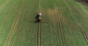 O pulverizador do trator fertiliza no campo com produtos químicos no campo da agricultura vídeos de arquivo