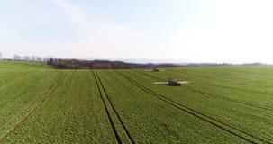 O pulverizador do trator fertiliza no campo com produtos químicos no campo da agricultura filme