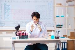 O químico novo que trabalha no laboratório imagens de stock
