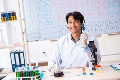 O químico novo que trabalha no laboratório foto de stock