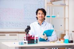 O químico novo que trabalha no laboratório imagens de stock royalty free