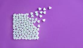 O quadrado feito de doces de açúcar branco em um fundo de papel roxo com corações voa afastado fotografia de stock royalty free