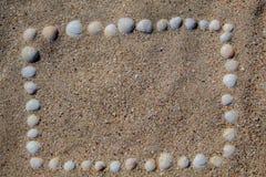 O quadro é apresentado na areia dos escudos, de cores e de formas diferentes imagem de stock