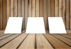 O quadro branco vazio do cartaz três pôs sobre a sala interior de madeira da textura velha do grunge para o produto atual, assoal Fotos de Stock