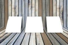 O quadro branco vazio do cartaz três pôs sobre a sala interior de madeira da textura velha do grunge para o produto atual, assoal Fotografia de Stock Royalty Free