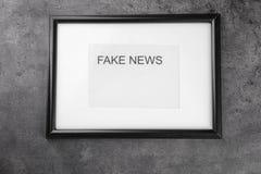 O quadro com palavras FALSIFICA NOTÍCIAS no fundo cinzento imagem de stock royalty free