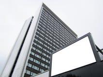 O quadro de avisos branco no fundo de um prédio de escritórios do arranha-céus, zomba acima imagens de stock