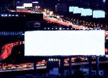 O quadro de avisos do espaço vazio na noite com tráfego de cidade e a luz do carro como o fundo, aprontam-se para a propaganda Fotografia de Stock