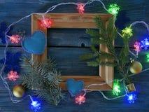 O quadro de madeira decorado com ramos do abeto, iluminação da Natal-árvore com flocos de neve, sentiu corações em um backgroun e fotos de stock