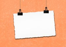 O quadro do papel vazio pendurou pelo grampo no fundo da parede do grunge Fotografia de Stock
