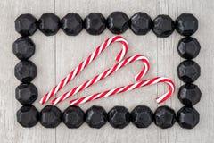 O quadro do retângulo do carvão deu forma a doces em um fundo de madeira lavado cinzento com os bastões de doces vermelhos e bran foto de stock