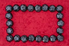 O quadro do retângulo do carvão deu forma a doces em um fundo vermelho de veludo foto de stock royalty free