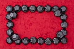 O quadro do retângulo do carvão deu forma a doces em um fundo vermelho de veludo imagens de stock royalty free