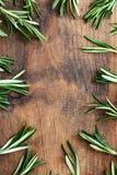 O quadro fez da erva fresca dos alecrins na placa de madeira Vista superior Copyspace imagens de stock
