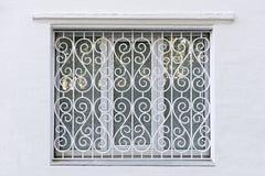 O quadro figurado da janela com ferro forjou o grating branco Imagem de Stock Royalty Free