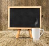 O quadro-negro com o copo de café quente branco na sala de madeira, zomba acima para fotos de stock royalty free