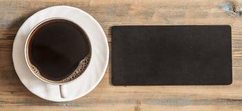 o quadro-negro vazio pequeno para seu texto, um copo do café quente corteja sobre imagens de stock