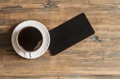 o quadro-negro vazio pequeno para seu texto, um copo do café quente corteja sobre imagem de stock