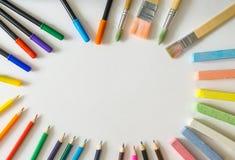 O quadro redondo, feito das escovas de pintura, canetas com ponta de feltro, cholks, coloriu lápis Fotografia de Stock Royalty Free