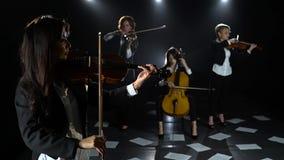 O quarteto de cordas que joga em uma sala escura no assoalho é folhas dispersadas com notas Fundo preto video estoque