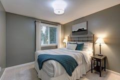 O quarto cinzento vangloria-se da grande cama do ferro fotos de stock