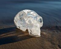 O quartzo claro cinzelou estrangeiro maia alongado Crystal Skull que coloca na areia molhada no nascer do sol foto de stock royalty free