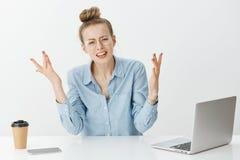 O que está acontecendo Mulher de negócios questionada frustrante nos vidros e na camisa do colarinho azul, mãos de espalhamento e Fotografia de Stock Royalty Free