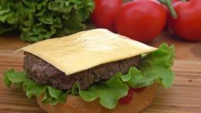O queijo cheddar é colocado em um hamburguer vídeos de arquivo