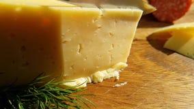 O queijo cortou com um aperitivo da faca em uma tabela de madeira tradicional, tiro do lento-movimento filme