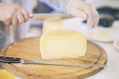 O queijo dirige no contador do mercado, queijo das vendas do vendedor, cabeças do queijo do corte na placa de madeira do mercado  Imagens de Stock Royalty Free