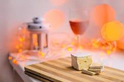 O queijo do brie corta o vidro do close up e de vinho com bokeh na tabela decorada fotos de stock