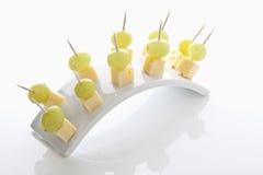 O queijo e as uvas no dente escolhem no fundo branco Imagem de Stock