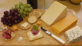 O queijo e os biscoitos seriram em uma placa de madeira Imagens de Stock