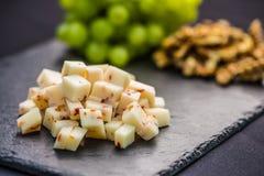 O queijo remenda uvas suculentas e as nozes na ardósia embarcam foto de stock royalty free