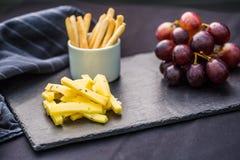 O queijo remenda uvas suculentas e as nozes na ardósia embarcam imagem de stock royalty free
