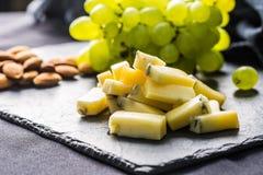 O queijo remenda uvas suculentas e as nozes na ardósia embarcam fotografia de stock royalty free