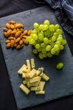 O queijo remenda uvas suculentas e as nozes na ardósia embarcam foto de stock