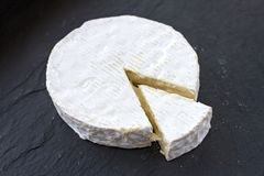 O queijo suíço temperado formado do camembert e uma fatia triangular dela em um fundo preto Foto de Stock