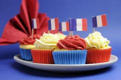 O queque francês do vermelho do tema, o branco e o azul mini endurece com as bandeiras de França - ascendente próximo. Imagem de Stock Royalty Free