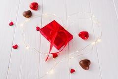 O querido do Chocolate-amor do Valentim deu forma a doces de chocolates com caixa de presente em um fundo de madeira branco foto de stock