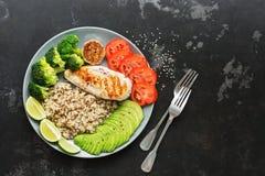 O quinoa da bacia da Buda, brócolis, grelhou a galinha, tomate no fundo de pedra preto Alimento integral saudável O conceito do e fotos de stock