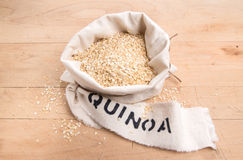 O Quinoa lasca-se em um saco de creme da tela com etiqueta escrita Imagem de Stock Royalty Free