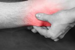 O quiroprático /physiotherapist que faz uns pés faz massagens o vermelho, dor co imagem de stock royalty free
