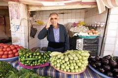 O quitandeiro cumprimenta seu cliente que está atrás de seus vegetais na loja pequena no bazar. Iraque, Médio Oriente. Fotografia de Stock