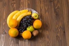 O quivi, laranjas, uvas, bananas está no prato Imagens de Stock