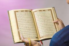 O Qur& aberto x27; é guardado pela mão que guarda os grânulos de oração & o x28; tasbih& x29; O Qur& x27; é o livro sagrado fotografia de stock