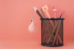 o r 与火鸟和铅笔的笔在珊瑚色的背景的篮子与赠送阅本 免版税图库摄影