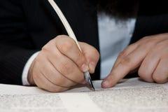 O rabino escreve a letra no rolo de Torah Imagens de Stock Royalty Free